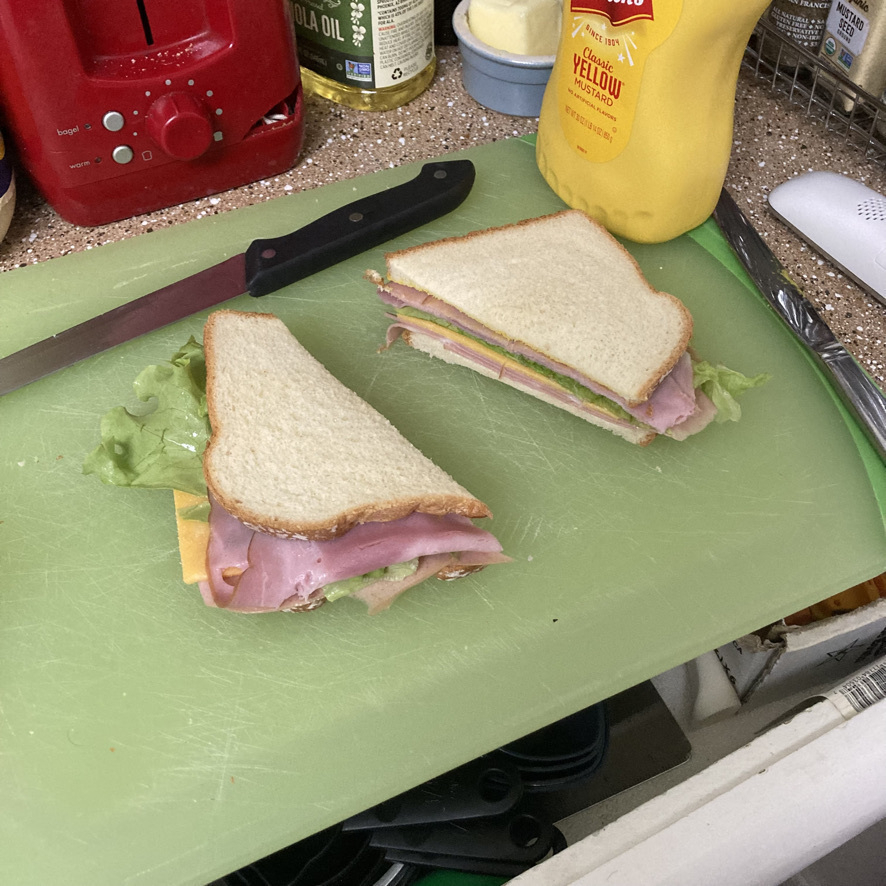 Ham and montedelo sandwich with mustard and mayo.