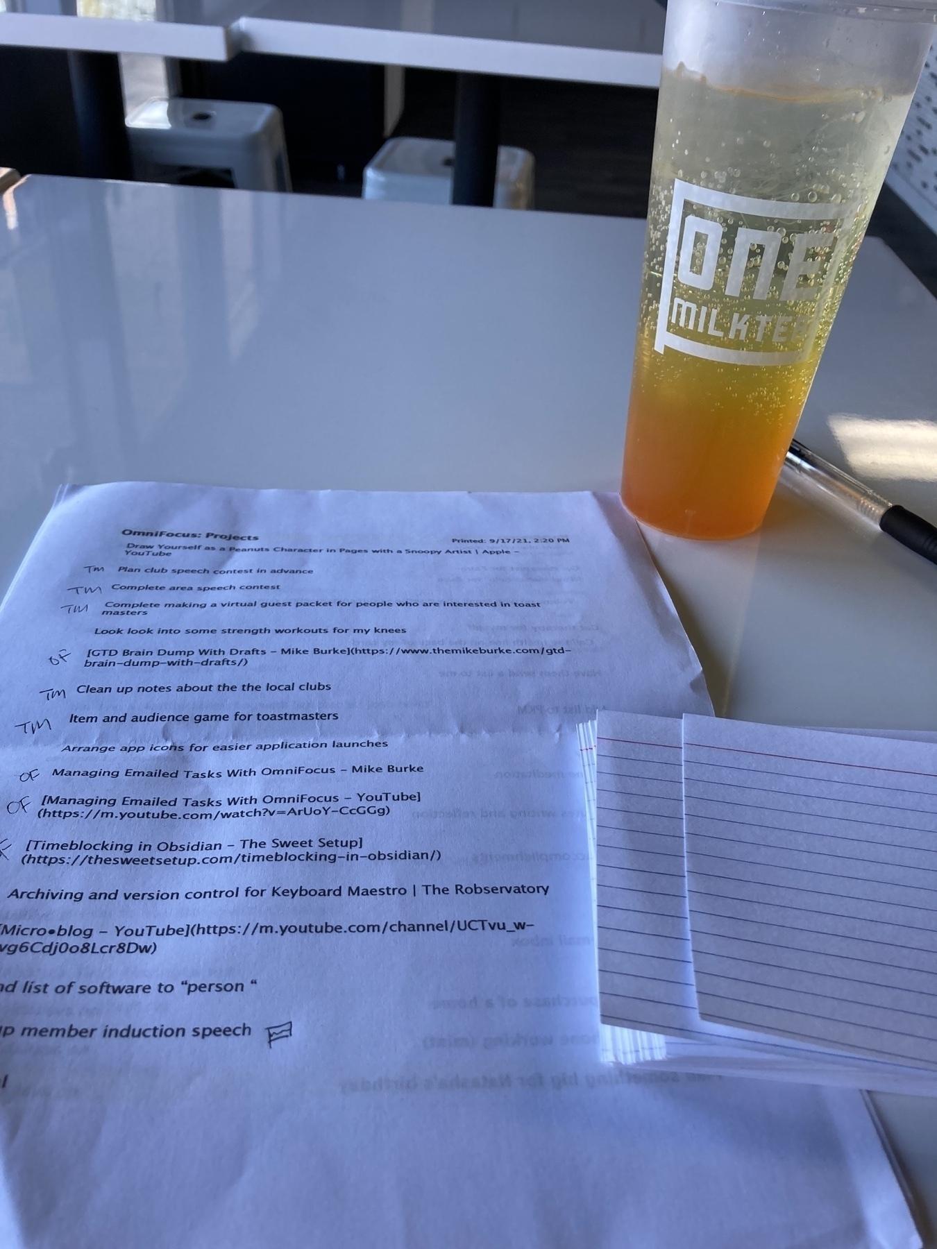 Tasks list next to a orange drink.